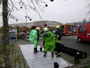 Kameraden der Feuerwehr schlüpfen in ihre Schutzanzüge. Foto: Thomas Steingen